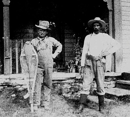 an old image of 2 men standing in front of a house with snowshoes