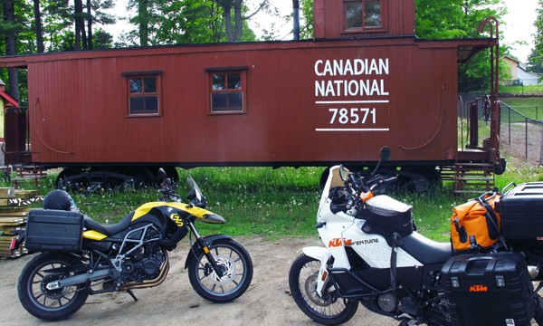 Two motorcycles in front of a rail car