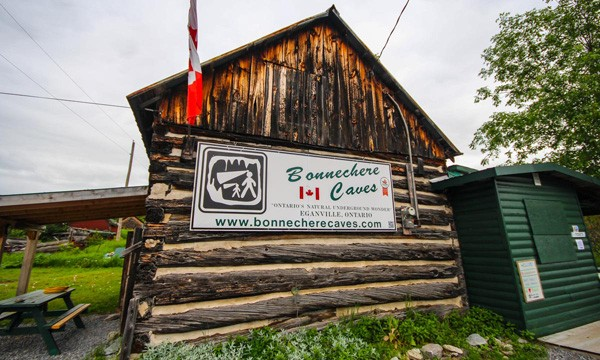 Log Building with Bonnechere Caves sign
