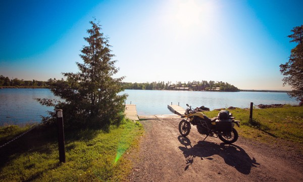 Motorcycle parked by the shoreline of a lake