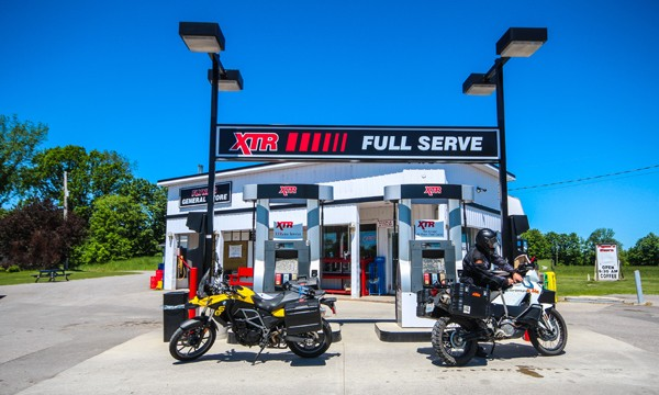 Two motorcycles at gas pumps