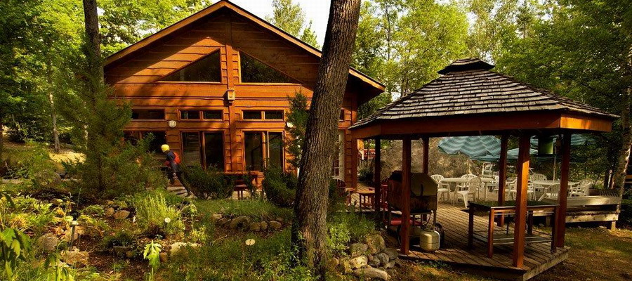 wood sided chalet and gazebo in forest