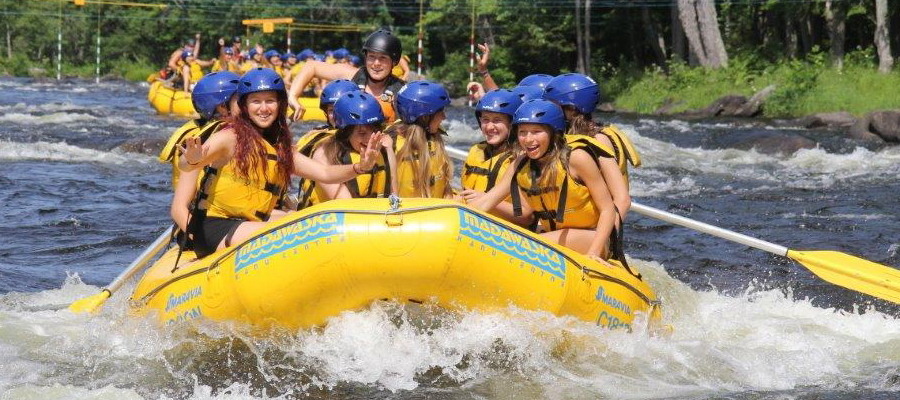 yellow raft on a river with smiling rafters