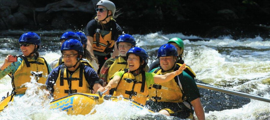 a raft going through rapids full of smiling rafters