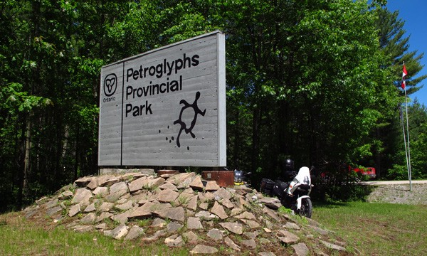 Motorcycle beside a sign that reads Petroglyphs Provincial Park