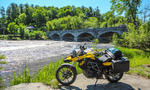 Motorcycle in front of a stone bridge