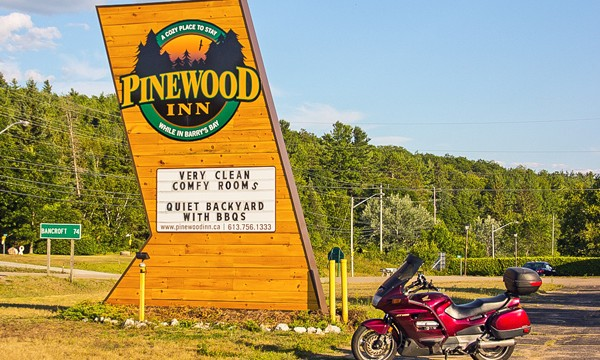 Motorcycle beside Pinewood Inn sign