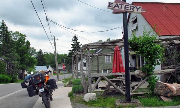 Motorcycle on sidewalk beside building with patio