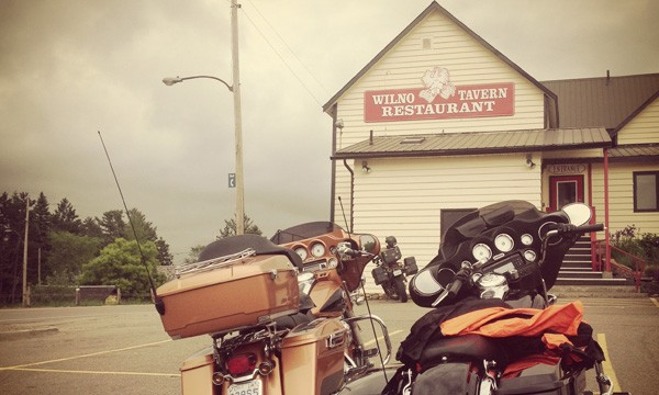 Two motorcycles in front of wooden building